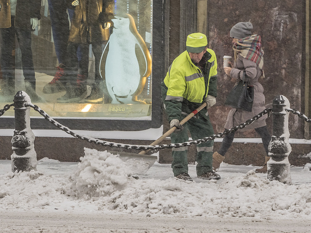 A street cleaner shoveling snow in a street in Saint Petersburg