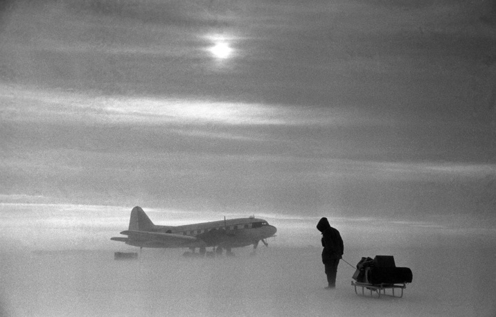 A polar explorer carrying cargo to an aircraft during snowstorm,1957