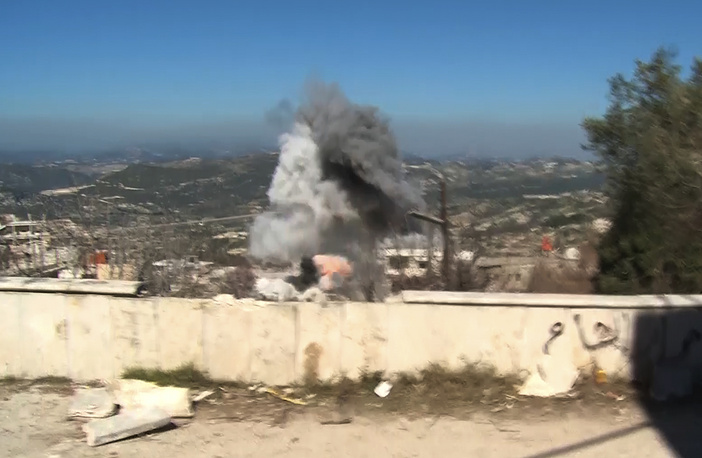 An artillery shell explodes about 150 meters away from a group of journalists