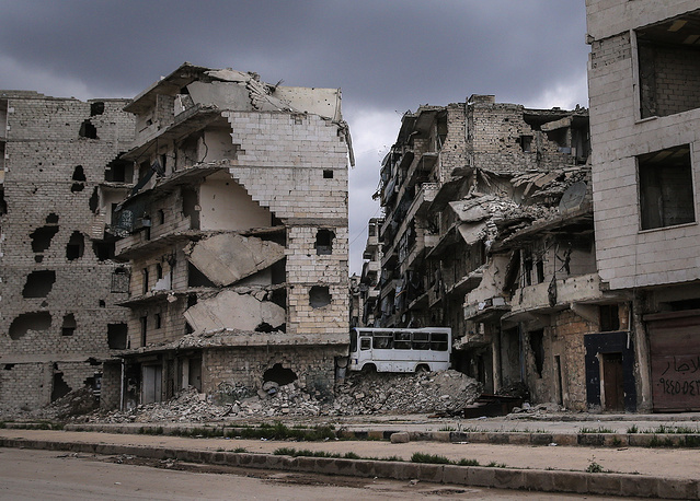 Destroyed apartment blocks and a bus used as a barricade in Aleppo