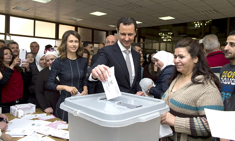 Syrian President Bashar Assad casting his ballot paper as his wife Asmaa at a polling station in Damascus