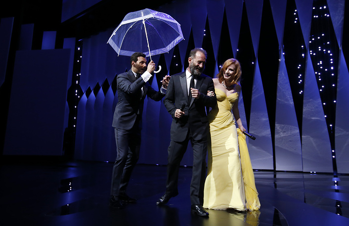 Master of Ceremony, French actor Laurent Lafitte holding an umbrella and French actor Vincent Lindon and US actress Jessica Chastain