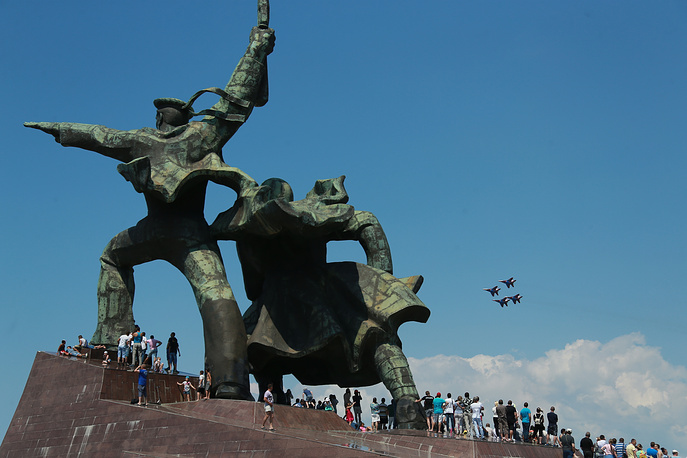 People at the base of the Sailor and Soldier monument watching MiG29 27 fighter jets from the Strizhi [Swifts] aerobatic team