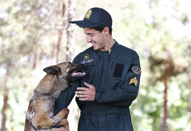 Iranian anti-drug police officer with his drug-sniffing dog in Tehran, Iran