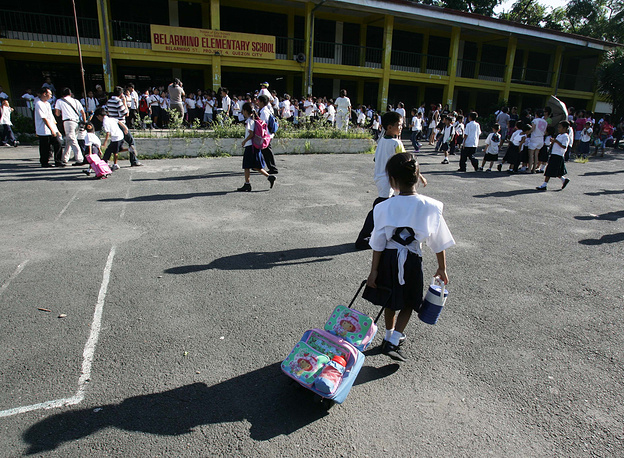 Elementary pupils gather at the premises of the closed Belarmino Elementary School at Manila's Quezon city,  Philippines