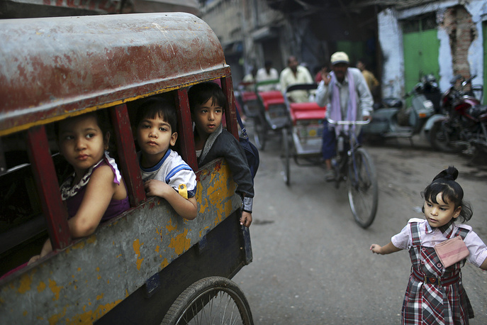 Indian school children wait in the back of a bicycle rickshaw as they head to school in New Delhi, India