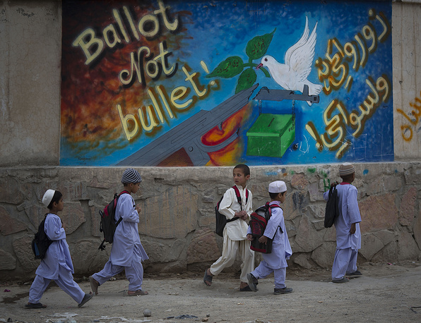 """School children pass by a graffiti reading, """"ballot not bullet"""" on their way on the outskirts of Kandahar, southern Afghanistan"""