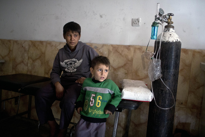 Children who have inhaled sulfur fumes wait for treatment at a hospital in Qayyarah, outside Mosul