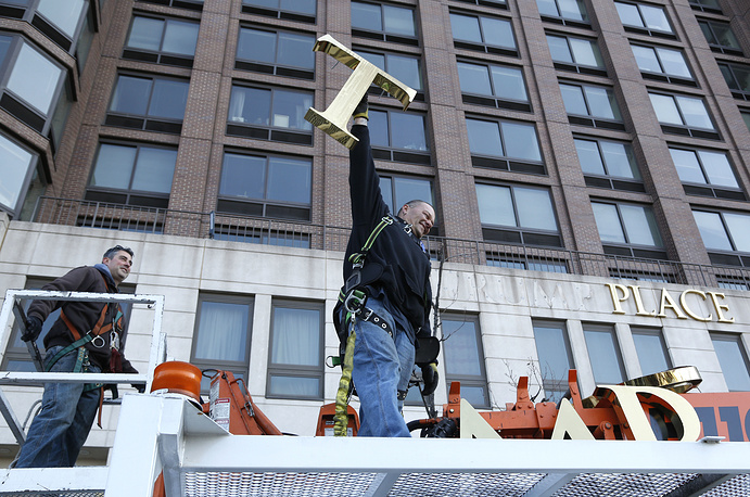 """A workman with letter """"T"""" as they remove the letters from a building formerly known as Trump Place in New York, November 16"""