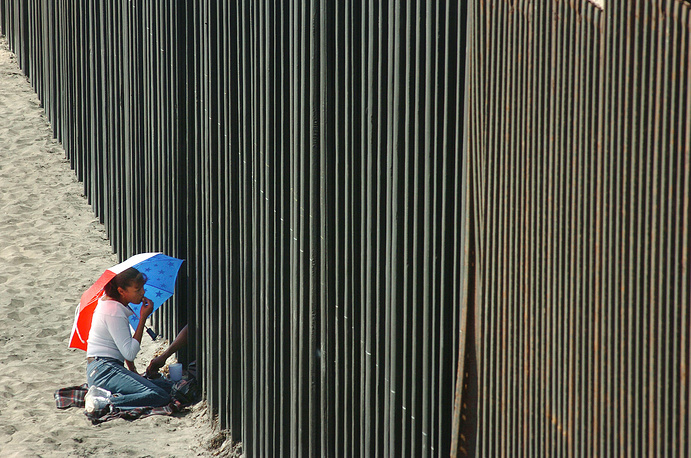 Woman shares a picnic lunch through the US-Mexico border fence with her husband in Tijuana, Mexico, 2006