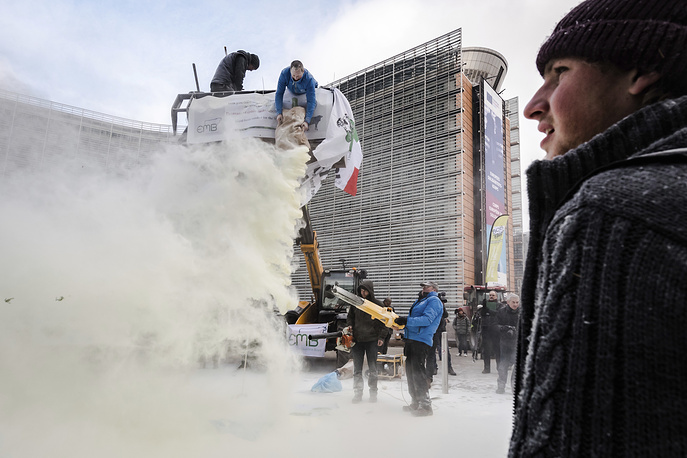 European dairy farmers spray the EU Council building with milk powder to protest the crisis in their sector, in Brussels, January 23