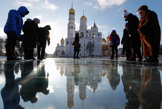 Visitors look through the Moscow Kremlin's museum windows at the Maly Nikolayevsky Palace foundation part on display in Ivanovskaya Square in Moscow, January 25