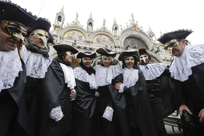 A masked group stands in San Mark's square in Venice