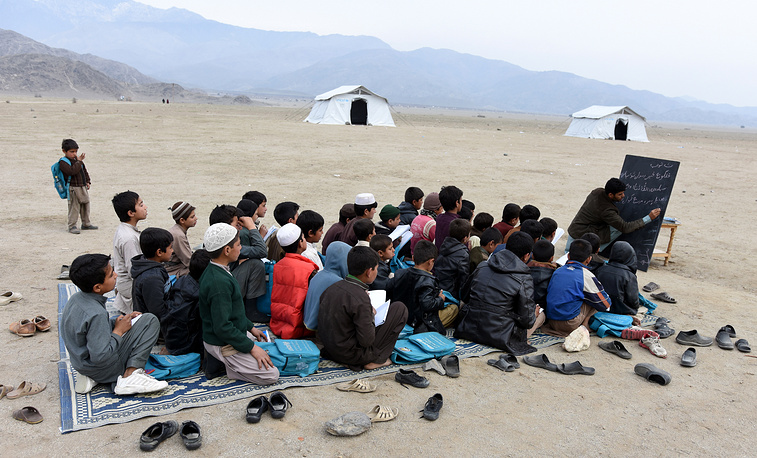 Afghan refugees, who have voluntarily returned from neighboring Pakistan, attend an open-air school outside their temporary shelters in Laghman province, Afghanistan, February 16