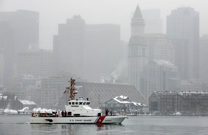 A US Coast Guard boat patrols on Boston Harbor as snow falls