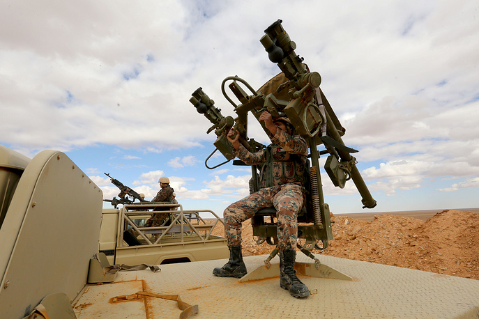 Jordanian soldier mans a gun mounted on a vehicle as Jordanian forces take position near the informal Rugban refugee camp at the Jordan-Syria border point of Al-Rugban area, northeast of Jordan, March 14