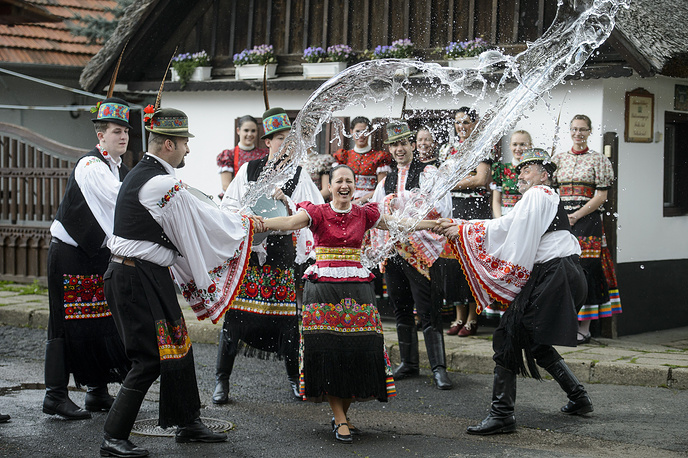 Men pour water from their bucket on a woman, all dressed in Matyo embroidered folk costumes typical to the region in Mezokovesd, to celebrate an old Hungarian Easter  tradition, Hungary, April 13