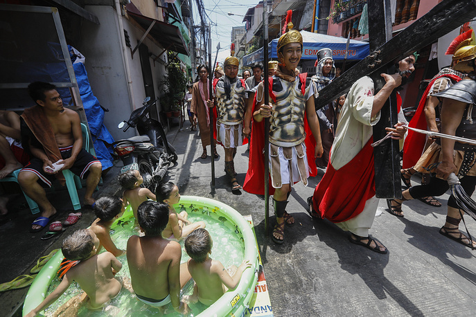 Children in a small pool watch man portraying a suffering Jesus Christ in a local community play called 'Senakulo' in Mandaluyong, Philippines, April 13