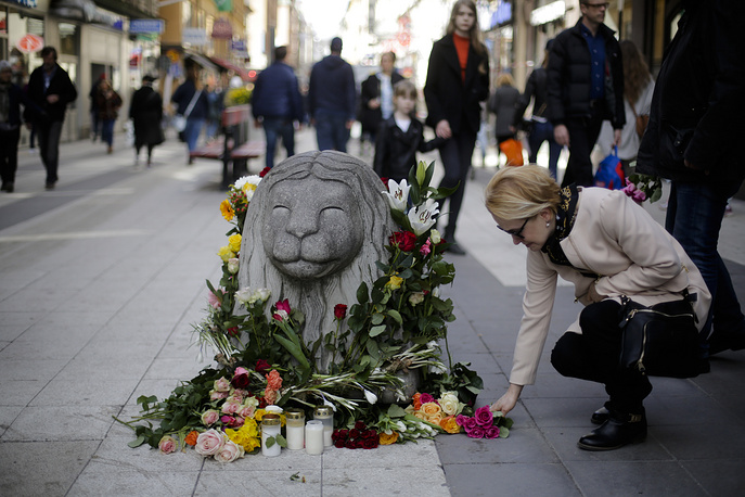 A woman lays down flowers near a stone lion on the reopened Drottninggatan street where a hijacked truck was driven into a crowd of pedestrians and crashed into the department store, in Stockholm, Sweden, April 9