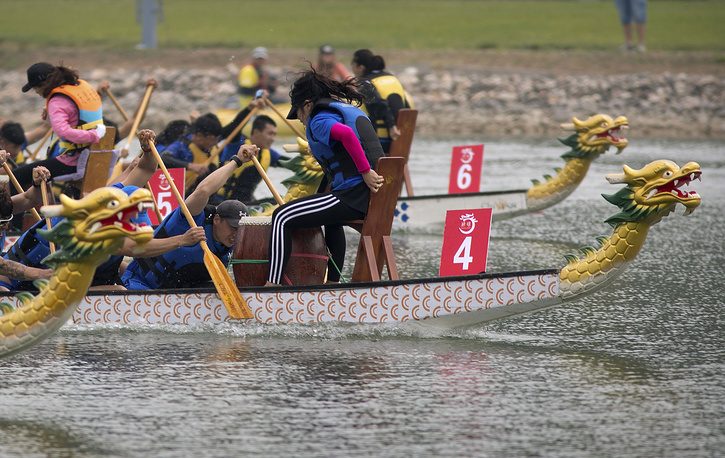 Teams of dragon boat racers paddle their boats at the Olympic Water Park in Beijing