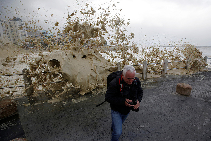 A man runs from sea spray as storms hit Cape Town, South Africa, June 7