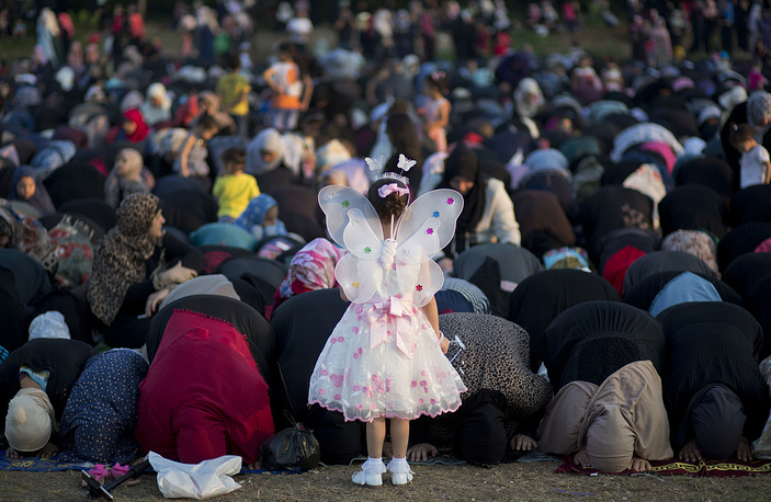 A Palestinian girl wears as a butterfly stand in front of women preforming at Eid al-Fitr prayers marking the end of the holy fasting month of Ramadan in Gaza City, June 25