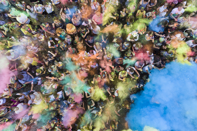 Young people throw coloured powder into the air during a festival of colours and glitter at the Severny airfield, Russia, July 1