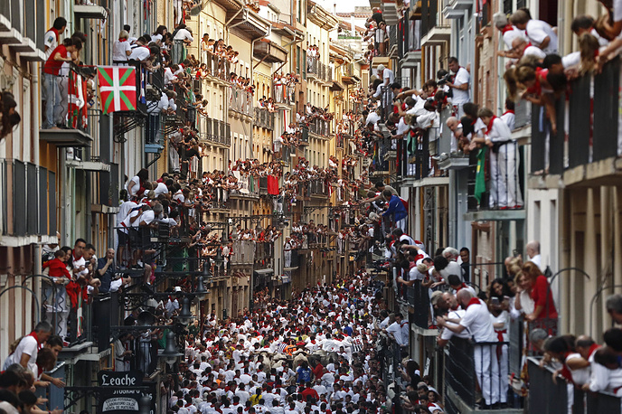 People observe from their balconies while bulls from the bull ranch Cebada Gago chase runners or 'mozos' during the first bull run of Sanfermines 2017