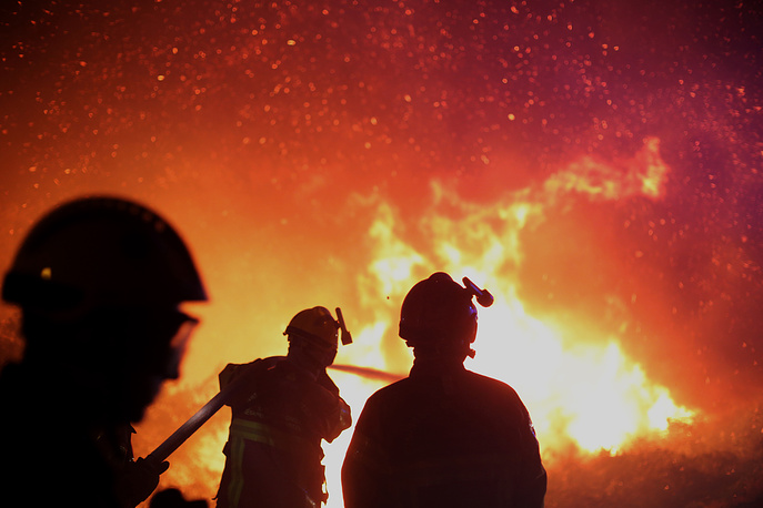 Firefighters spray water as they try to douse a fire near the village of Biguglia, Corsica island, France