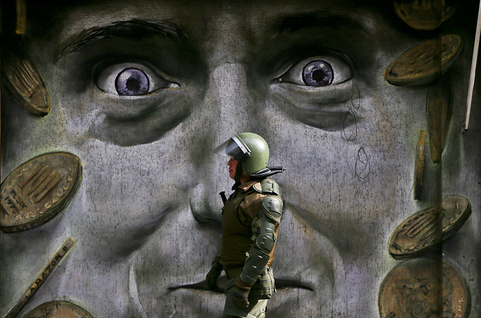 A police officer walks by a mural as police break up a protest, that was blocking a street and demanding an end to the current Pension Fund Administrators system in Santiago, Chile, July 24