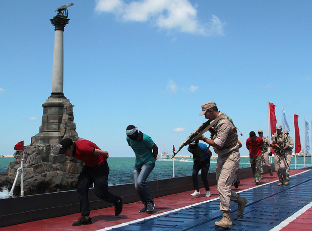Russian servicemen take pirates captive as part of the Russian Navy Day parade drills in Sevastopol, Crimea
