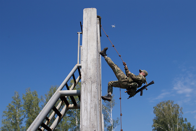 Russian soldier climbing over a wall during a team's run at the Army Scout Masters competition