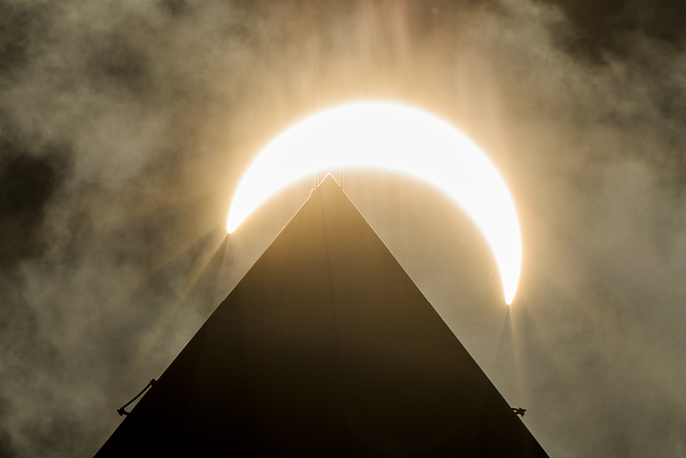 The moon eclipses the sun above the Washington Monument