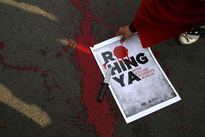 A Muslim protester picks up a poster as fake blood is seen spattered on the ground after a theatrical act depicting the violence against Muslim Rohingya in western Myanmar performed during a rally in Jakarta, Indonesia