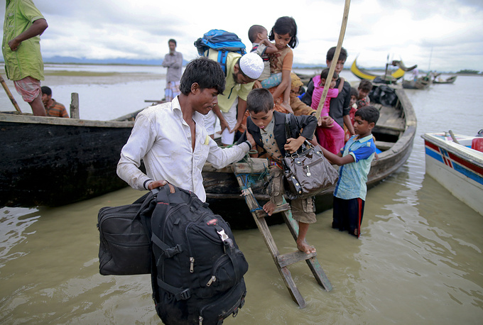 Members of Myanmar's Muslim Rohingya minority get down from a boat after crossing a canal at Shah Porir Deep, Bangladesh