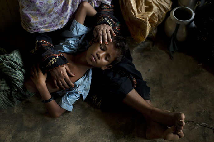 A Rohingya woman comforts her exhausted son as they take shelter inside a school after having just arrived from the Myanmar side of the border at Kutupalong refugee camp, Bangladesh, September 7