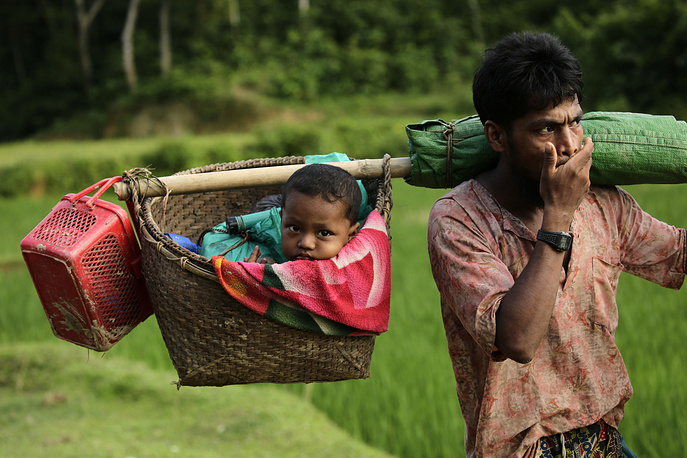 A Rohingya man carries his baby in a basket as he arrives in Tuangiri, Teknaf, Bangladesh, September 12