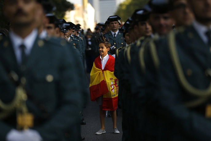 """A young boy, draped in the Spanish flag, stands amongst Spanish military personnel as they prepare for a military parade during the national holiday known as """"Dia de la Hispanidad"""" or Hispanic Day, in Madrid, Spain, October 12"""