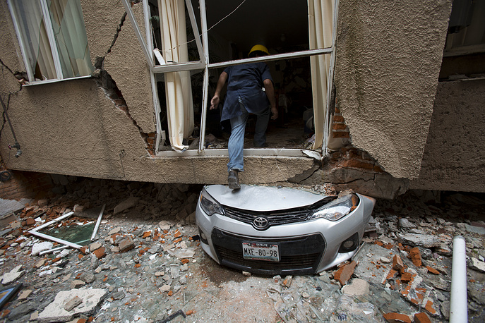 A man climbs over a crushed car into what was a second-story apartment at 517 Tokio street, felled by the earthquake almost one month ago in the Portales Norte neighborhood of Mexico City, Mexico, October 18