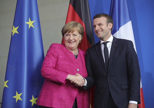 French President Emmanuel Macron and German Chancellor Angela Merkel shake hands after a press conference in Berlin, Germany, 2017