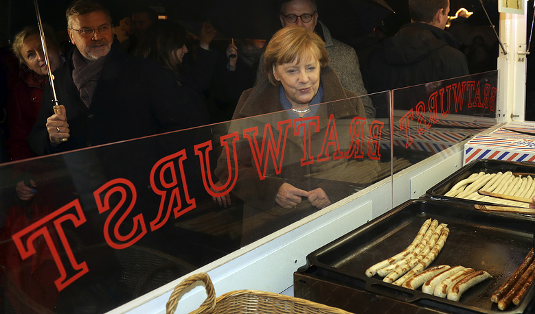 What's Cooking! German Chancellor Angela Merkel lured to a bratwurst stall in Berlin as she visits the Christmas market on the Breitscheidplatz at the Kaiser Wilhelm Memorial Church, Germany, December 12