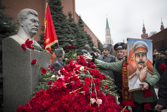 A woman holding a portrait of Stalin places flowers near the monument signifying Joseph Stalin's grave near the Kremlin wall marking the anniversary of Stalin's birth in Moscow's Red Square, Russia, December 21