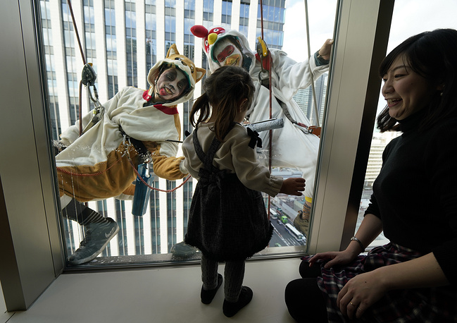 Window cleaners dressed as a dog and bird are greeted by a girl at Tokyo's Yaesu shopping and business district, Japan, December 20