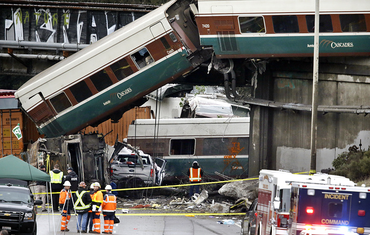 Cars from an Amtrak train lay spilled onto Interstate 5 below alongside smashed vehicles in DuPont, USA, December 18, 2017,Wash. The Amtrak train making the first-ever run along a faster new route hurtled off the overpass near Tacoma and spilled some of its cars onto the highway below