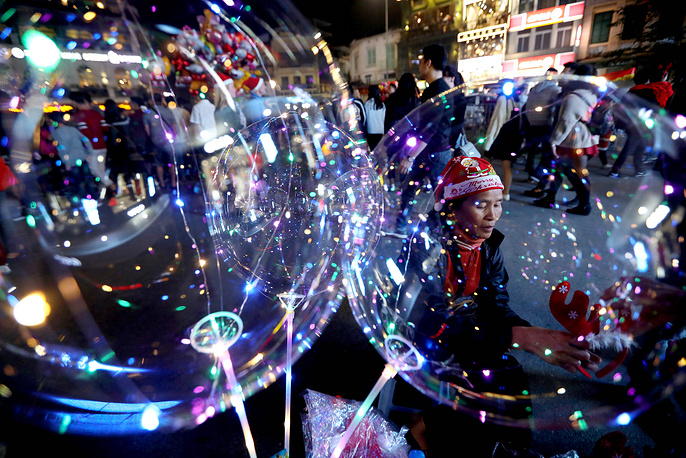 A woman selling balloons and Christmas decorations waits for customers at a street in Hanoi, Vietnam. Christmas is not an official holiday in Vietnam, however some of its customs have become more popular in recent years
