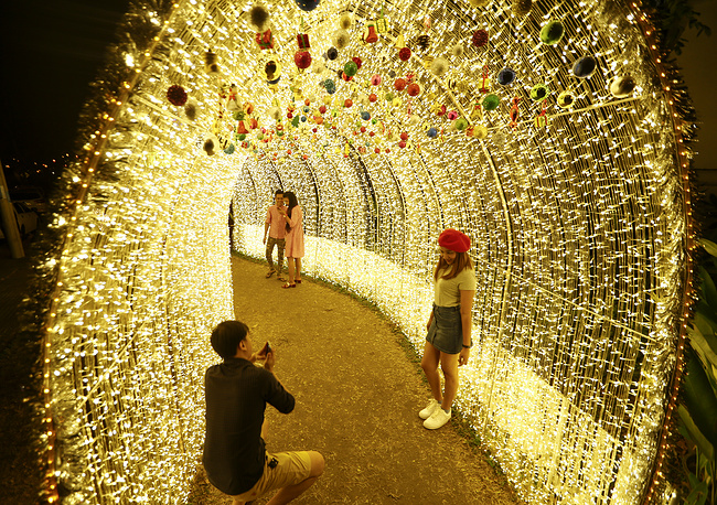 A couple take photographs near the decorations with Christmas lights in Yangon, Myanmar