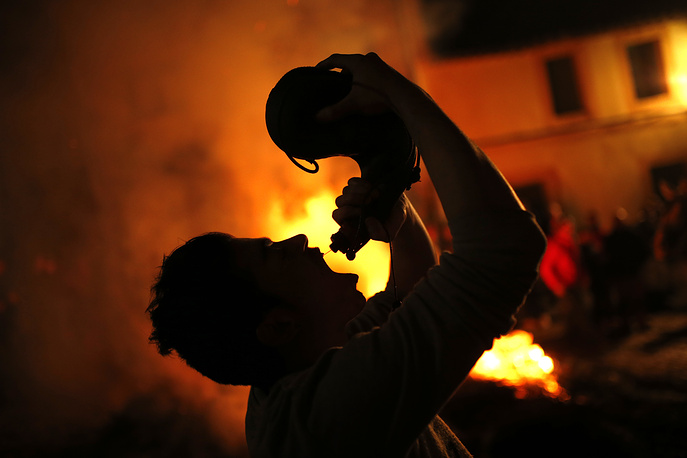 A man drinks wine from a wineskin next to bonfires during the ritual in San Bartolome de Pinares, Spain