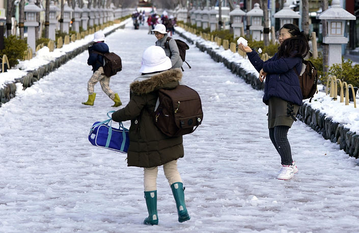 Schoolchildren play with snow in Kamakura, west of Tokyo