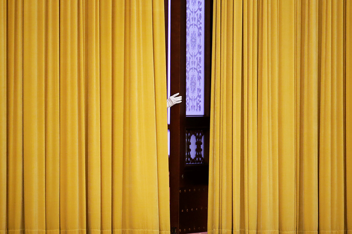 A member of staff appears from behind curtains before the visit of British Prime Minister Theresa May at the Great Hall of the People in Beijing, China, January 31