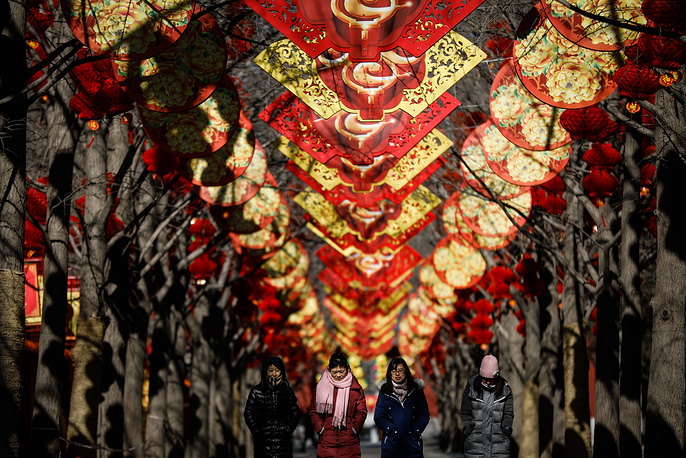 Chinese women walk past red lanterns hanging from trees to celebrate the upcoming Chinese Lunar New Year, at Ditan Park in Beijing, China, February 12